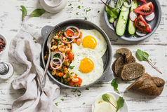 Fried egg, beans in tomato sauce with onions and carrots, fresh cucumbers and tomatoes, homemade rye bread - delicious breakfast. Or snack on light wooden royalty free stock photo