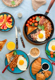 Fried egg, beans, tomatoes, bacon, toast various fruits, juice, Royalty Free Stock Photography