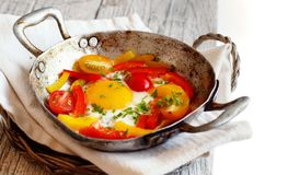 Fried egg with a bell pepper and tomatoes. On an old frying pan stock photography