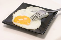 Fried egg on black dish Stock Photo