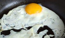 Fried egg in black pan closeup Stock Photos
