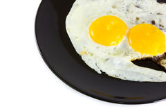 Fried egg. On black plate Stock Photos