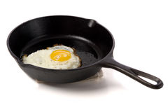 Fried Egg in a Black Skillet. A fried egg in a black iron skillet on a white background, food, nourishment concept Stock Photos