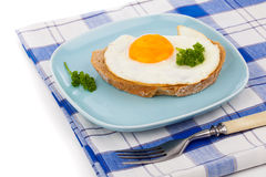 Fried egg in blue plate with fork Royalty Free Stock Photos