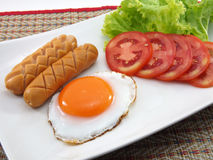 Fried egg with boiled sausages Royalty Free Stock Images
