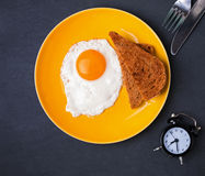 Fried egg and bread on the plate and alarm clock on the black ba Stock Photography