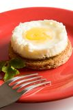 Fried egg on brown toast. Lying on the red dish stock images