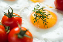 Fried egg with cherry tomatoes. Delicious and healthy breakfast. Sunny side up. Selective focus Royalty Free Stock Photo