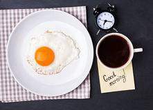 Fried egg, coffee and alarm clock on the black background Royalty Free Stock Images