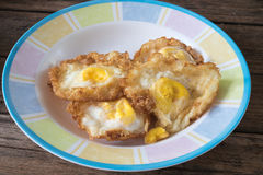 Fried egg. Crispy fried egg on a wooden table Royalty Free Stock Image