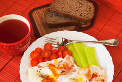 Fried egg with cup of tea. Fried egg setting with vegetable, bread and cup of tea Royalty Free Stock Images