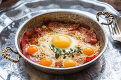 Fried egg and cured meat in copper pan, close view Royalty Free Stock Images