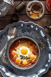 Fried egg with cured meat, traditional turkish breakfast, served in metal dishware, rustic Royalty Free Stock Photo