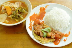 Fried egg dressing chili sauce on rice eat with Thai mixed vegetable curry sweet and sour soup Stock Photo