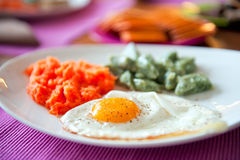 Fried egg with dumplings and grated carrot Stock Photos