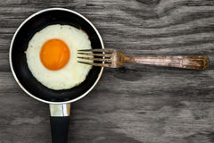 Fried egg and fork on wooden background Stock Photo