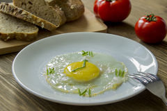 Fried egg in form of a clock. Breakfast: Fried egg in form of a clock, tomato and bread with fork Stock Photo