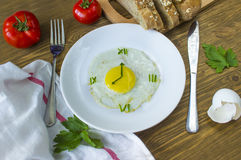 Fried egg in form of a clock. Breakfast: Fried egg in form of a clock, tomato and bread with fork and knife Stock Photography