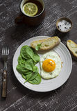 Fried egg and fresh spinach on a white plate Stock Photo