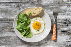 Fried egg and fresh spinach on a white plate Royalty Free Stock Images