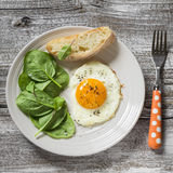 Fried egg and fresh spinach on a white plate on a light wooden background Royalty Free Stock Photo