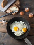 Fried egg in a frying pan served with whole wheat bread. On a wooden background royalty free stock photo