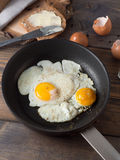Fried egg in a frying pan served with whole wheat bread. On a wooden background stock photo