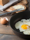 Fried egg in a frying pan served with whole wheat bread. On a wooden background royalty free stock photography