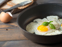 Fried egg in a frying pan served with whole wheat bread. On a wooden background stock photography