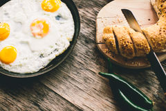 Fried egg in a frying pan. On a wooden table stock photo