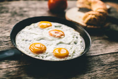 Fried egg in a frying pan. On a wooden table royalty free stock photo