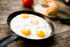 Fried egg in a frying pan on wooden table. Fried egg in a frying pan on a wooden table royalty free stock photography