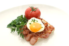 Fried egg on grilled bacon. And tomato Stock Images