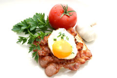 Fried egg on grilled bacon. Tomato and garlic Stock Photography