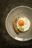 Fried egg and grilled sausage on grey plate Stock Photo