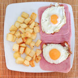 Fried egg with ham and roast potato cubes Royalty Free Stock Photos