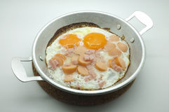 Fried egg with ham and sausage in a pan Royalty Free Stock Photo