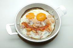 Fried egg with ham and sausage in a pan Stock Photo