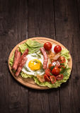 Fried egg with ham and tomatoes on old wooden table Stock Photo