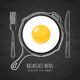 Fried egg and hand drawn outline watercolor pan, fork and knife on textured black board background. Royalty Free Stock Photo