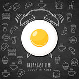 Fried egg and hand drawn watercolor alarm clock on textured black board background with outline food icons. Stock Image