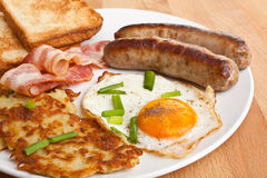 Fried egg, hash browns and bacon breakfast. Plate with classic fried egg, hash browns and bacon breakfast on a wooden table stock photography