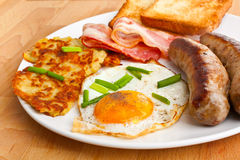 Fried egg, hash browns and bacon breakfast Stock Photo