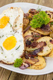 Fried Egg on a heap of roasted Potatoes Stock Photography