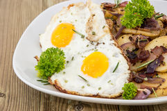 Fried Egg on a heap of roasted Potatoes Stock Image