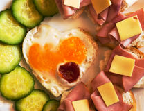 Fried egg on heart. Shaped toast with cucumber and ham for Valentine's Day Stock Photos