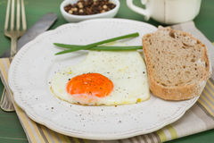 Fried egg heart with onion and bread. On white plate Royalty Free Stock Photos