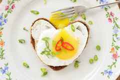 Fried egg heart rye sandwich with scallion, chili and fork on wh Stock Images