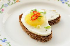 Fried egg heart rye sandwich with scallion and chili on white pl Royalty Free Stock Photography