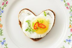 Fried egg heart rye sandwich with scallion and chili on white pl Royalty Free Stock Images